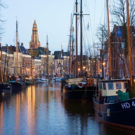 Winter Welvaart in Groningen, aan de Hoge en de Lage der Aa liggen historische zeilschepen afgemeerd. Versierd met lampjes en met diverse kraampjes aan de kade is er een gezellige ontspannen sfeer.